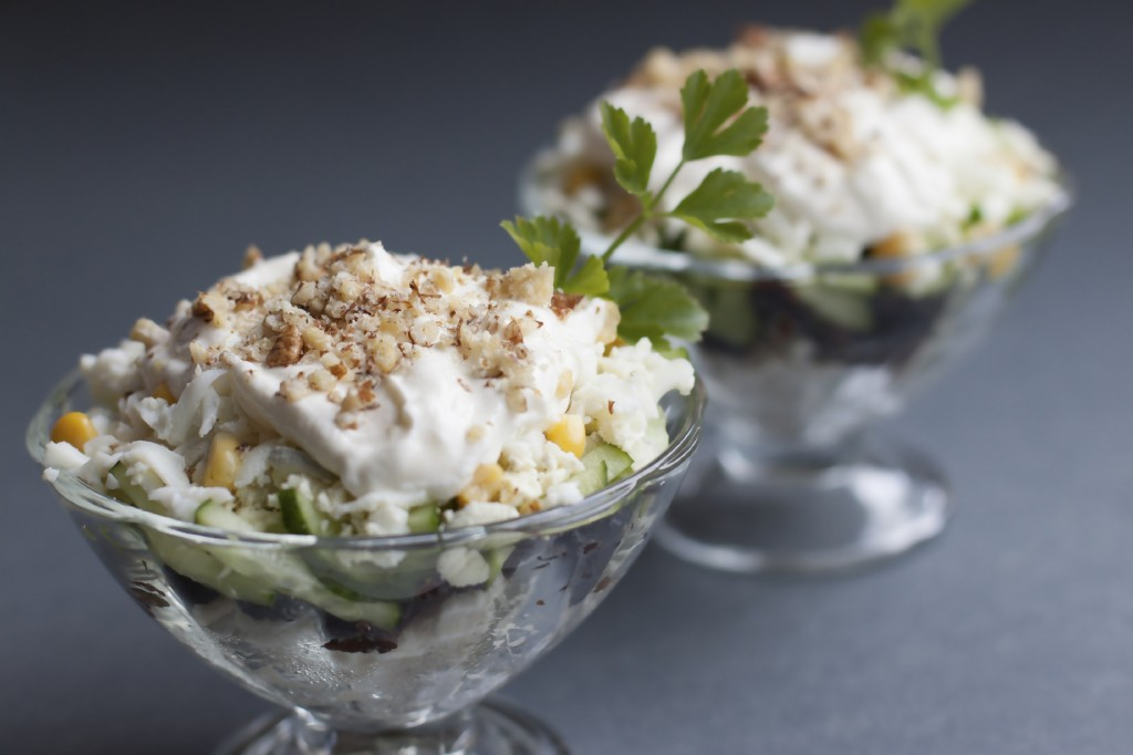 Salad with chicken meat, prunes, cucumbers, boiled egg, walnuts with a sauce of sour cream and mayonnaise.