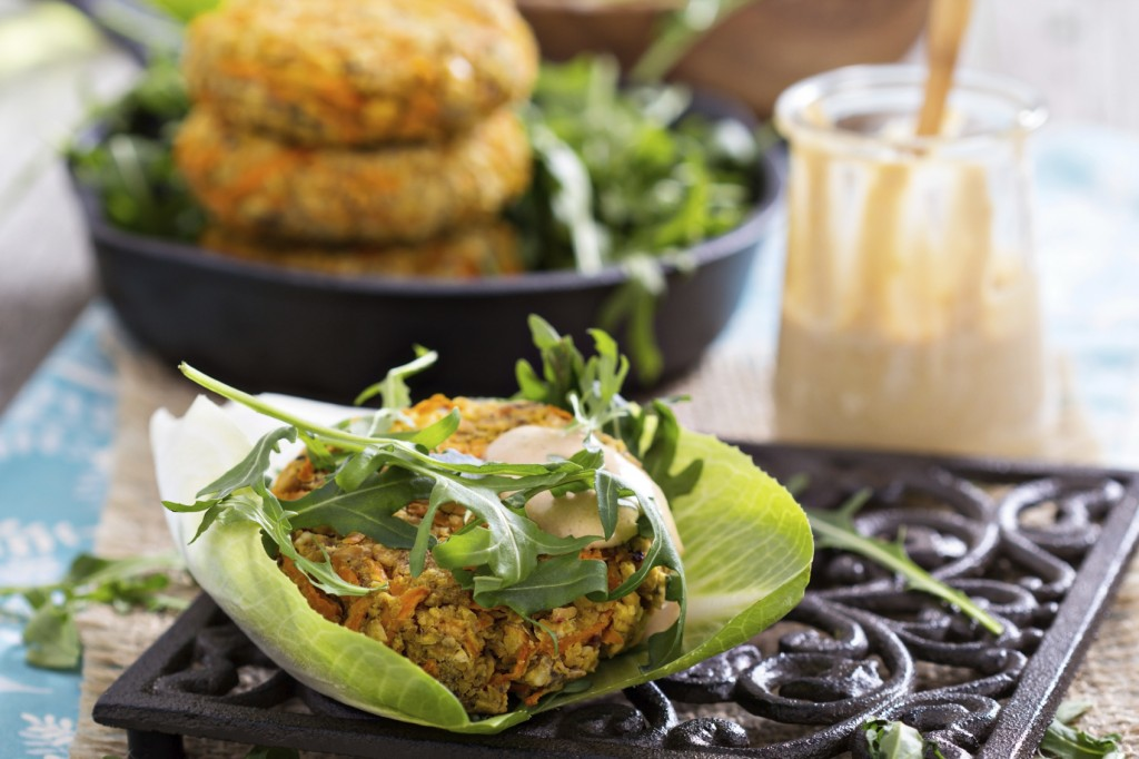 Vegan burgers with sweet potato served with arugula and peanut sauce